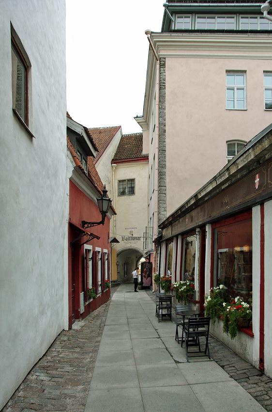 Foto de uma rua estreita com um café à direita, com duas mesas na rua e decorações de flores nas janelas