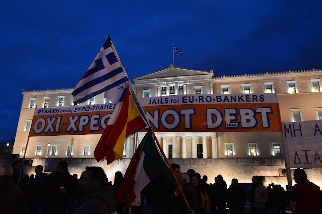 "Greeks demonstrate in front of the country's parliament on February 16, 2015 in a pro-government demonstration after Athens rejected an initial EU bailout offer as ""absurd"" and ""unacceptable"" (AFP Photo/Louisa Gouliamaki) Banner written in Greek and English reads: Jail for Euro Bankers Not Debt"