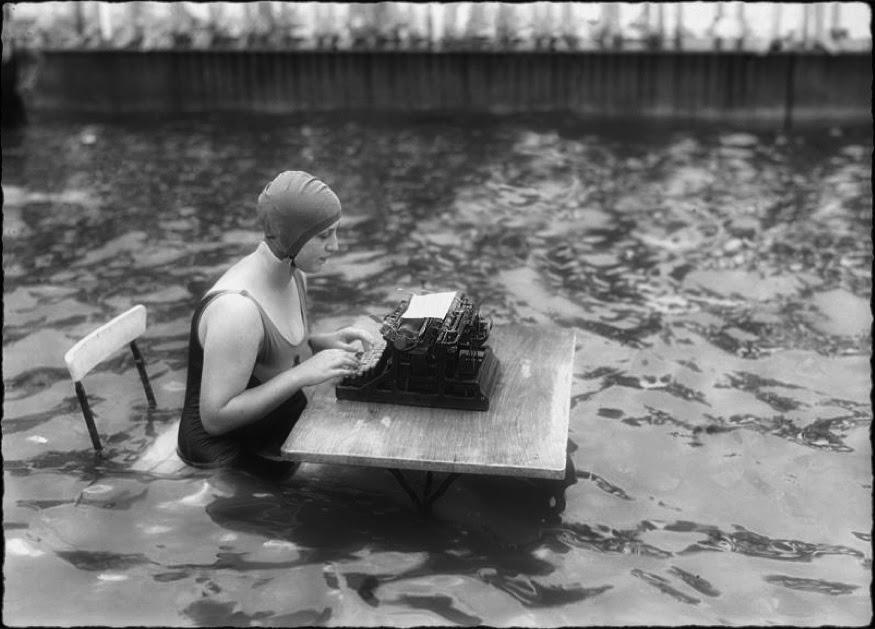 Eine Frau, die eine Badekappe und einen Badeanzug trägt, sitzt auf einem Klappstuhl und tippt in eine alte Maschine, die vor ihr auf einem Klappstuhl steht. Dabei sitzt sie bis zum Bauch im Wasser eines großen Beckens oder Kanals.