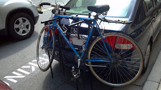 blue panasonic bicycle on the back of a car