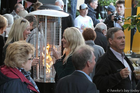 Blondes L-R: Libby Bradford, Napier, Jayde Corlett, Napier, enjoying the heat from the patio gas heater - Street Alley, a mini street food market, a F.A.W.C! Food and Wine Classic event at Milk and Honey Restaurant, Ahuriri, Napier. photograph