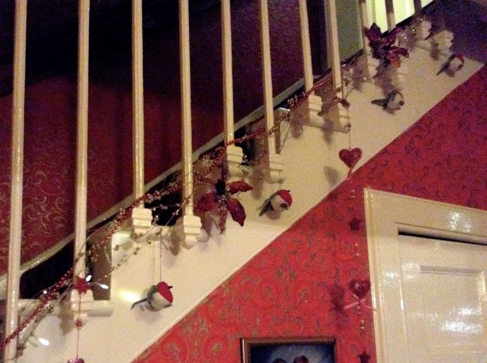 Christmas decorations on stairs - robins, flowers, red & gold beading and dangling hearts