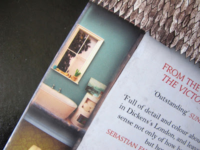 Back cover of a book, showing a picture of a miniature bathroom.