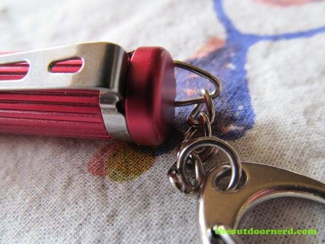 Olight I3S AAA flashlight - closeup of steel clip and keychain on the red version