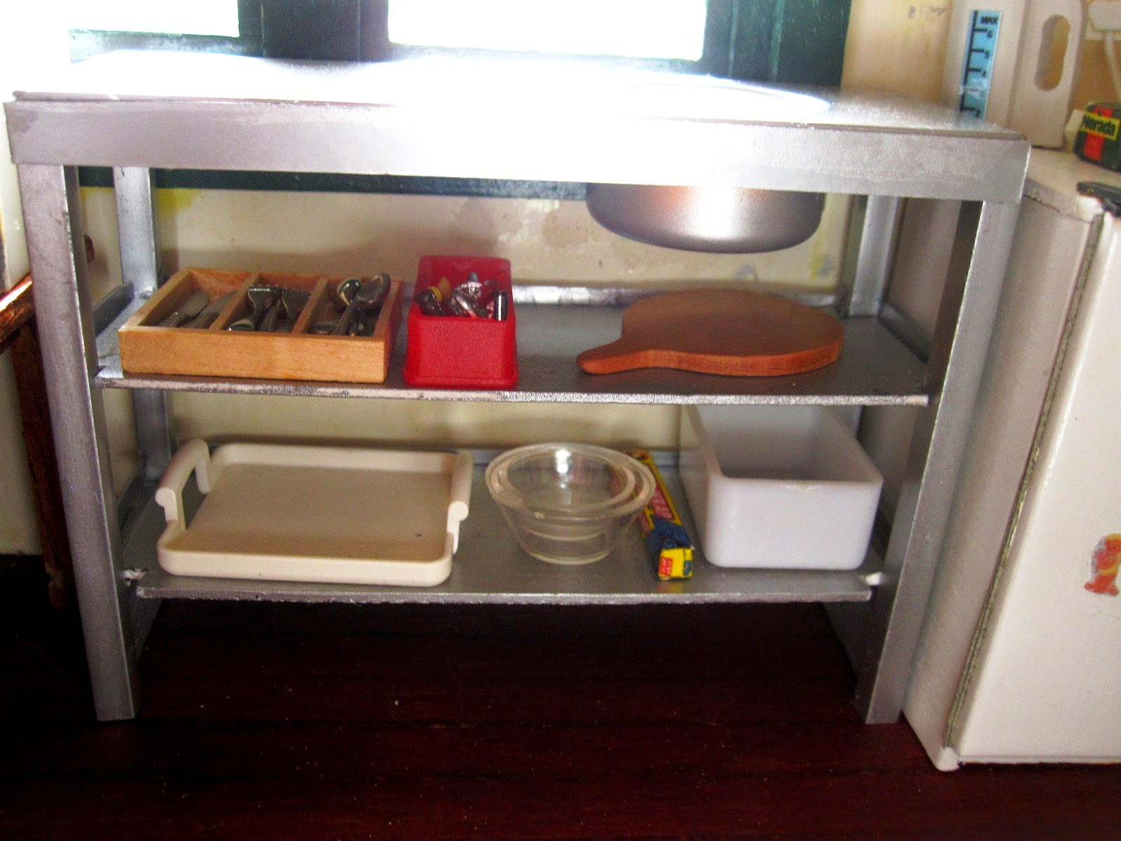 Modern miniature metal kitchen bench unit displaying a selection of kitchenware underneath.