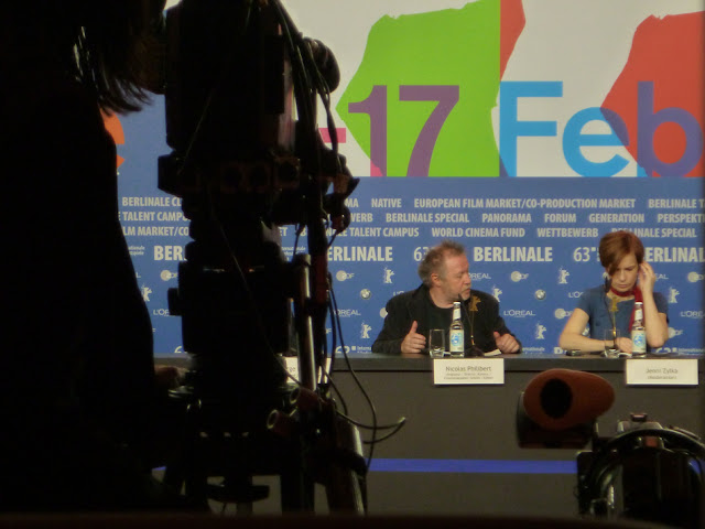 Pressekonferenz. Im Anschnitt eine Filmkamera als schwarze Silhouette