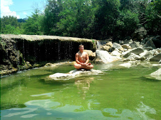 Austin sitting quietly with a waterfall behind him