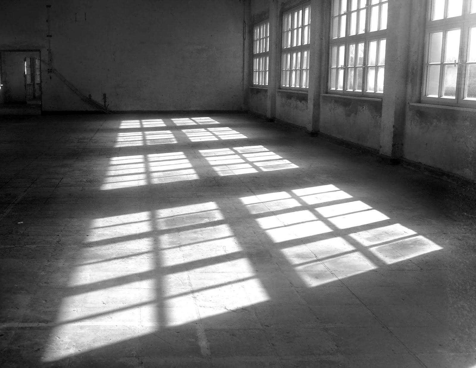 Reflektierendes Sonnenlicht auf dem Boden der ehemaligen Schneiderei. Der Raum ist leer.