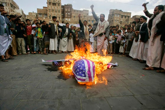 Yemenis burn a replica of a fighter jet draped with an American flag.