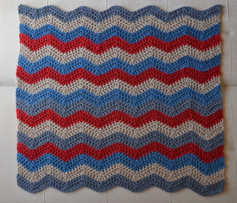 Ripple blanket complete but unblocked. 17 stripes (34 rows).The colours from bottom to top (in order of crochet): grey, camel, blue, red, grey, camel, red, grey, blue, camel, red, blue, camel, red, blue, camel and grey.