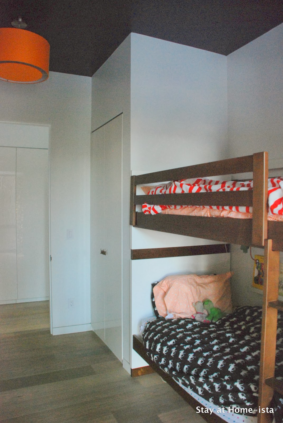 Bunk room with a navy ceiling and orange drum shade