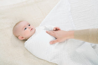 Left hand side of swaddle is folded over.
