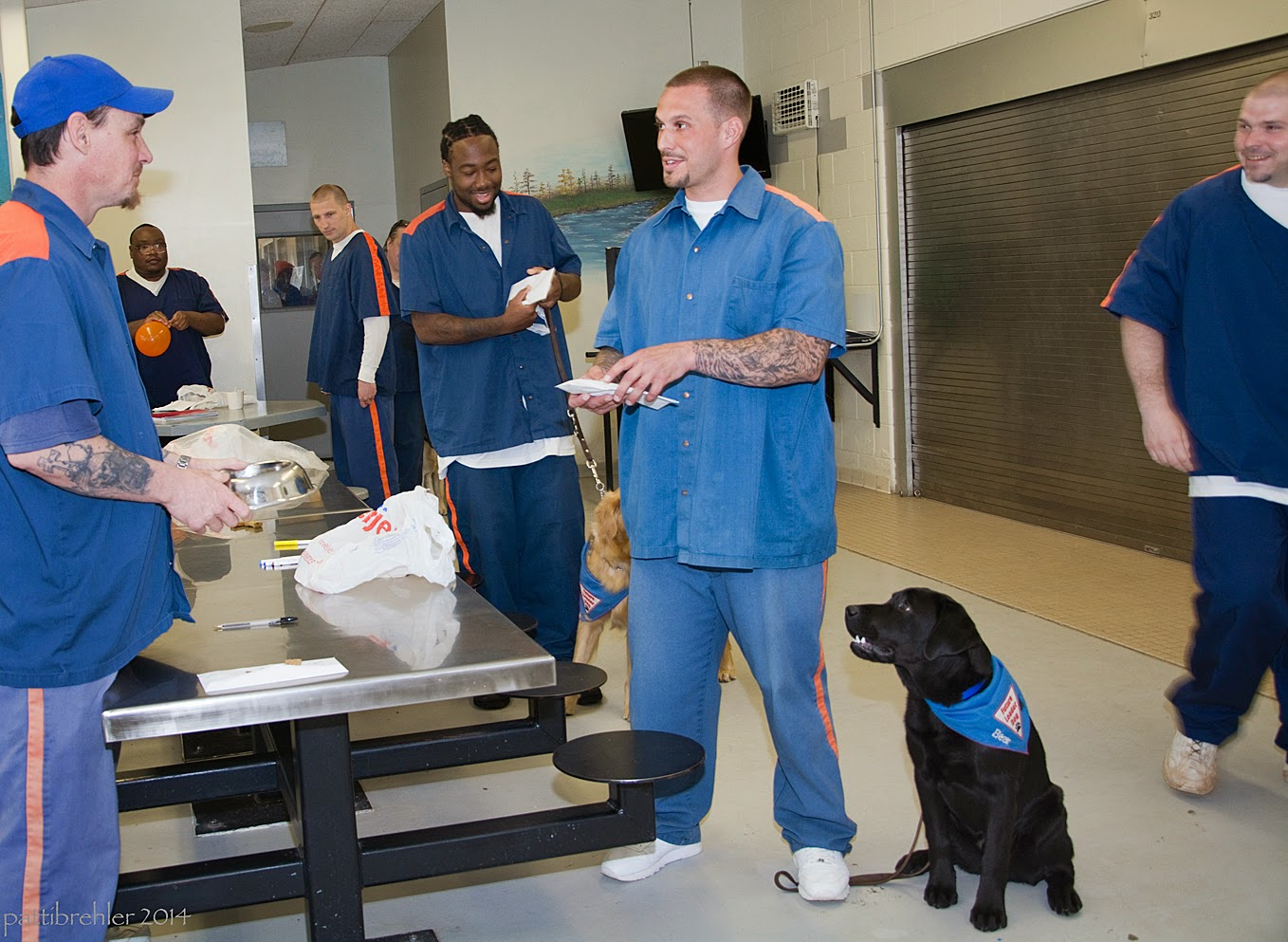 The same man is standing to the left with the dog bowl. This time he is looking at a different man standing opposit from the table on the right side. The man on the right is reaching into the white envelope with his left hand. He is standing on the leash of the black lab puppy that is sitting on his left side looking up at him. The puppy is wearing the blue Future Leader Dog bandana. More men are in line in the bacground, and one man on the far right is wallking by smiling at the men standing. There is a white plastic bag on the table.