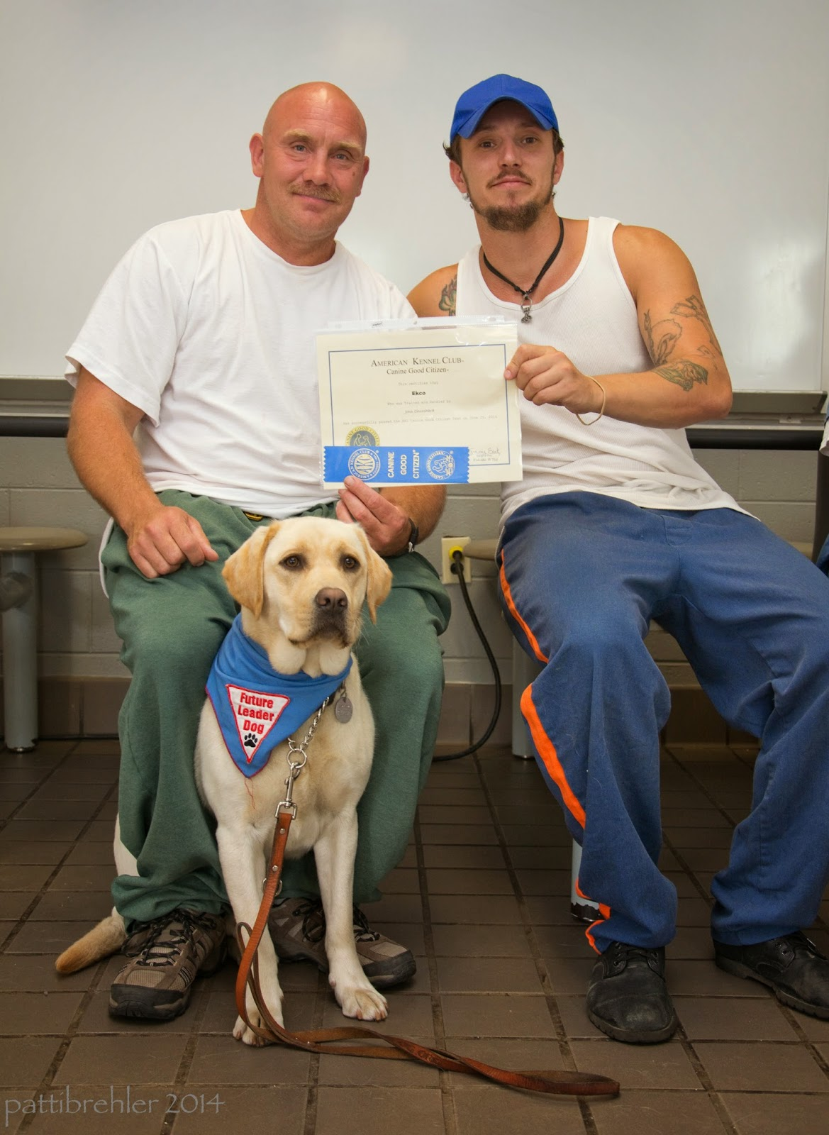 Two men are sitting down behind a yellow lab, who is sitting on the tile floor in front of the man on the left. The man on the left is wearing green pants and a white t-shirt. The man on the right is wearing blue prison pants and a white tank shirt and a blue baseball cap. The men are holding up a certificate between them.