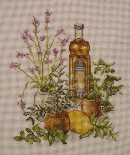 Cuadro de punto de cruz para la cocina con hierbas aromáticas, aceite y limón
