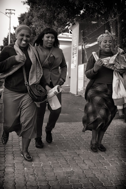 Three women laugh as they walk down Kloof Street in Cape Town in this street photograph