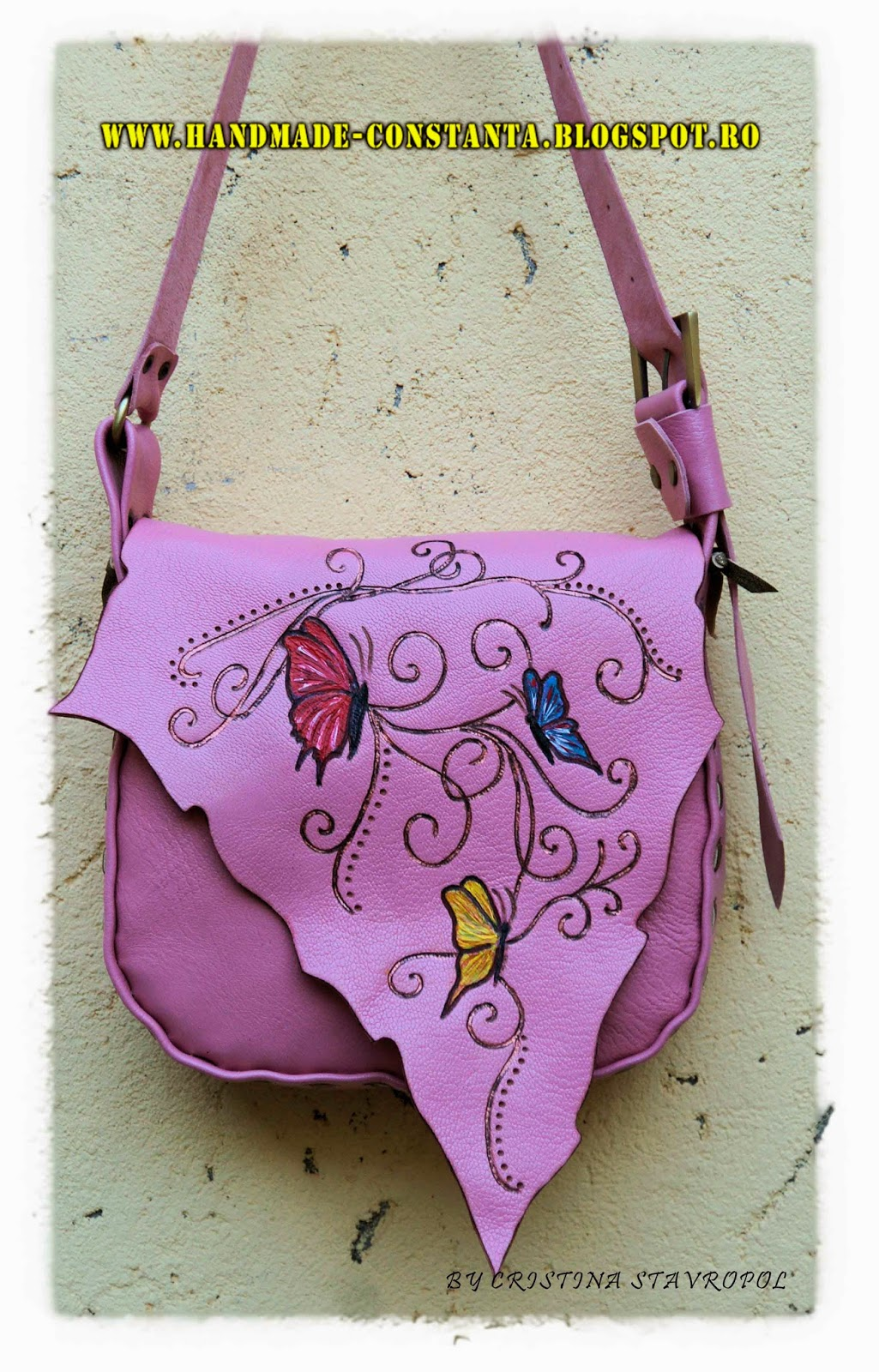 Pale pink leather bag with butterflies.