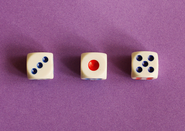 three dice on purple background