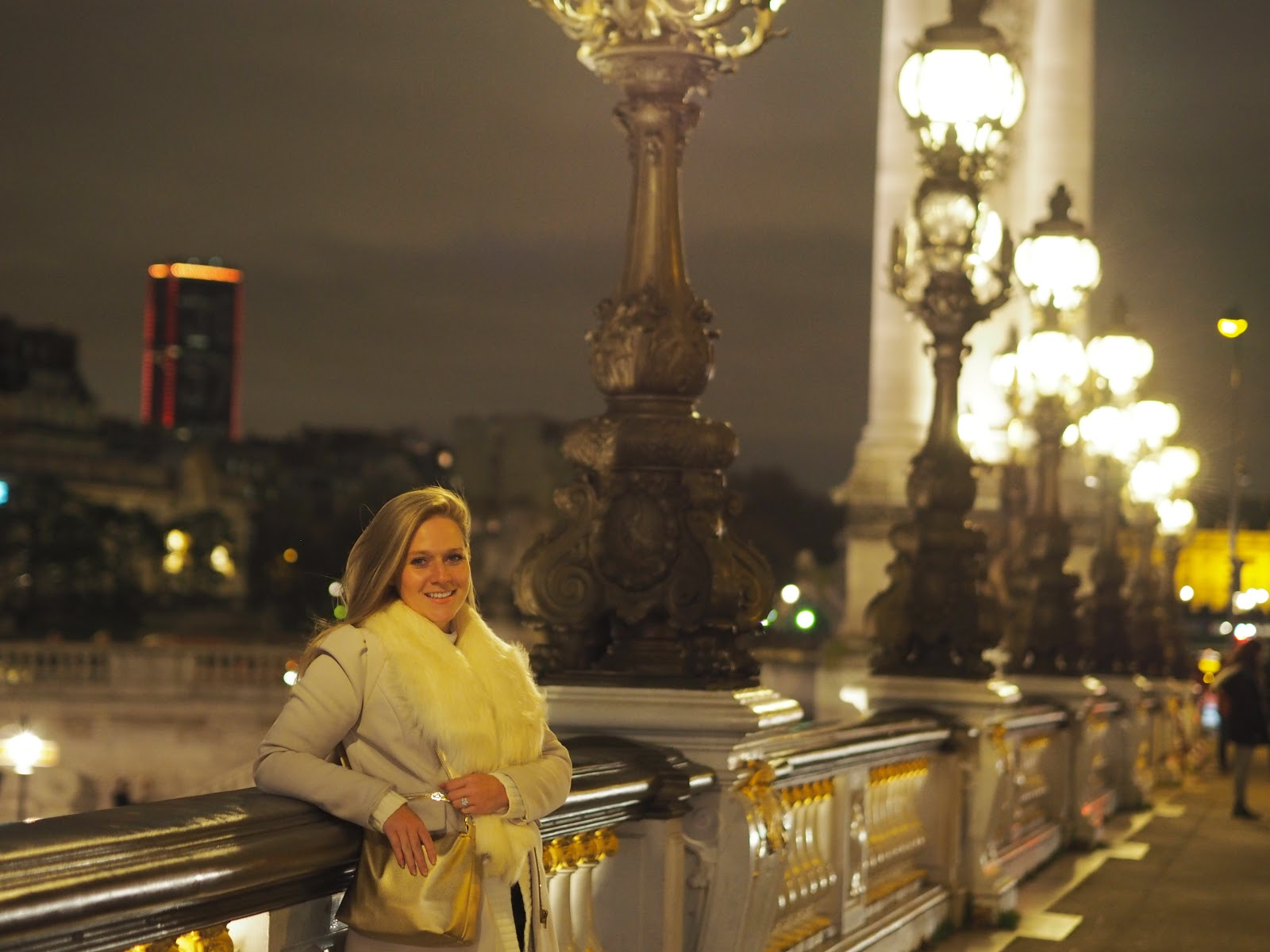 Girl standing on golden bridge at night, Paris