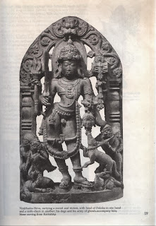 Virabhadra-Shiva, carrying a sword and trident, with head of Daksha in one hand and a rattle-drum in another his dogs and his army of ghouls accompany him; Stone carving from Karnataka