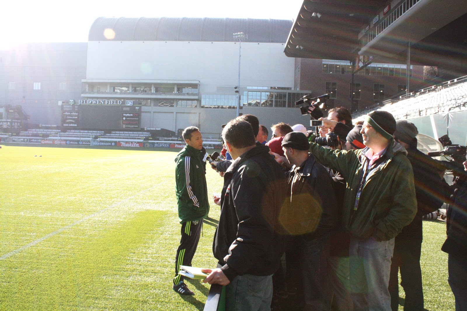 Bunch of media types shoving microphones and cameras in Caleb Porter's face. Lots of lens flare.