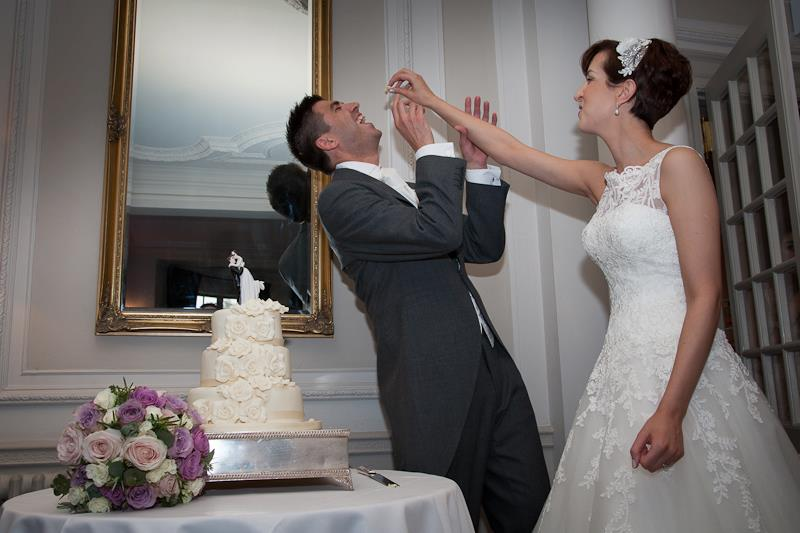wedding cake, cutting the cake, bride and groom, wedding dress, wedding flowers