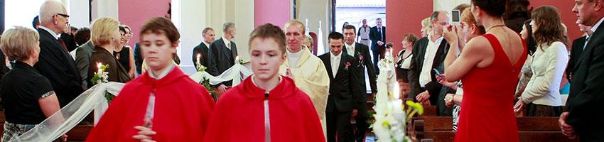 ministranci ksiądz i para mloda idą przez kościół