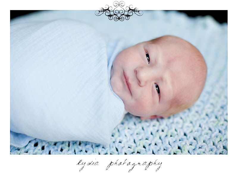 Baby boy wrapped in a blanket at lifestyle newborn portraits at William Jessup University in Rocklin, California