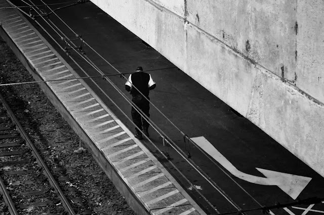 A train security guard walks along the platform framed by parallel lines
