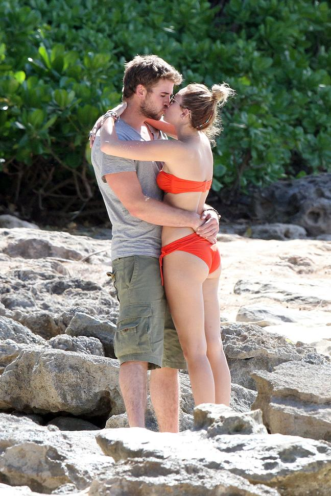 Miley Cyrus kissing Liam Hemsworth in an orange bikini