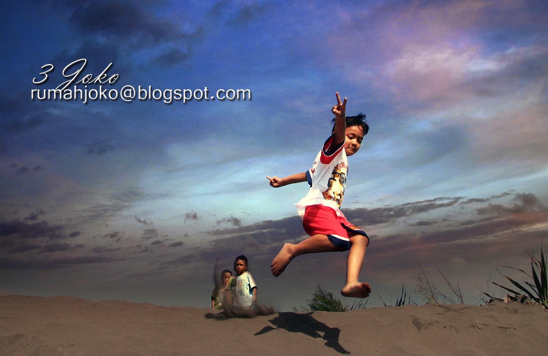Lompat di gundukan pasir di pantai Depok