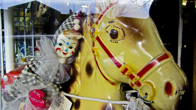 A Denver window display with a creepy clown riding a horse.