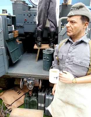 1/6 scale German soldier drinking coffee in diorama of an army post on display at a scale model exhibition.