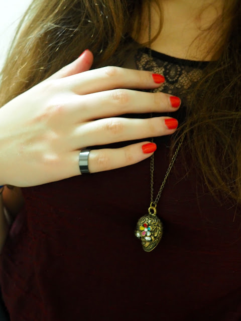 Something Wicked | outfit jewellery details of gold sugar skull pendant necklace, plain black metal ring, and bright red nail polish