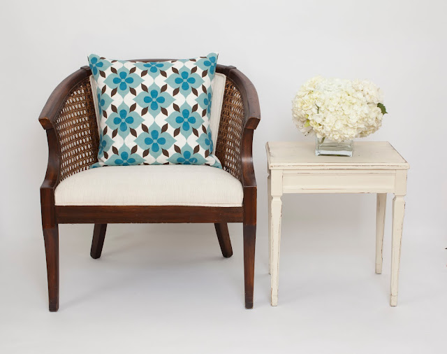 Nbaynadamas Coco's Flower pillow on a classic cane chair next to a white vintage side table with white hydrangeas