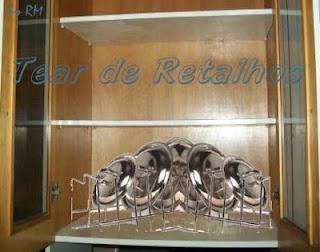 Tampas de panelas guardadas em pé em um utensílio tipo escorredor de pratos