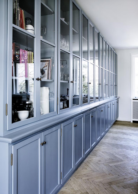 close up of cabinets with glass panes in a blue kitchen with herringbone wood floors