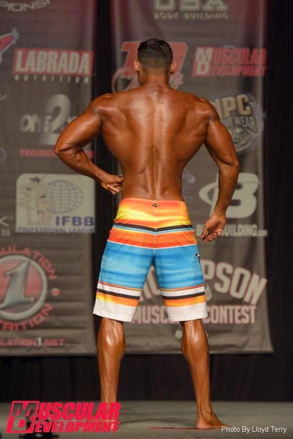 Atleta Men's Physique faz pose de costas durante a sua apresentação. Foto: Terry Lloyd / Muscular Development