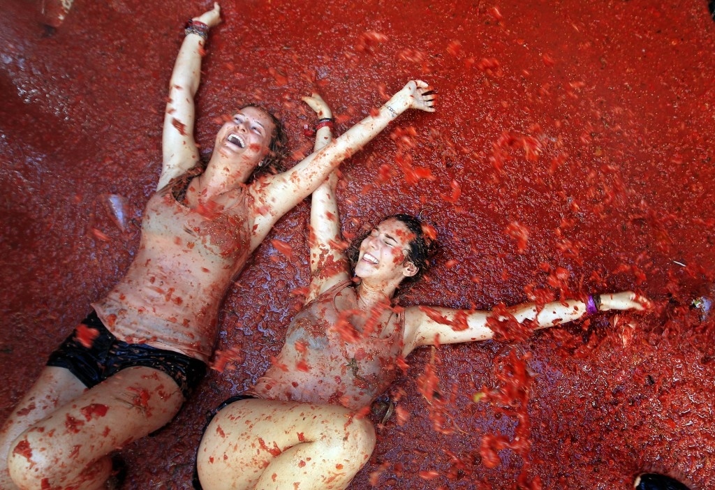 70 Of The Most Touching Photos Taken In 2015 - Two women lie in a puddle of squashed tomatoes during the annual