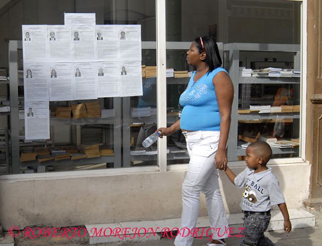 Una mujer observa las fotos y biografías de los candidatos al Parlamento Cubano expuestas en la calle Obispo, en La Habana, Cuba.