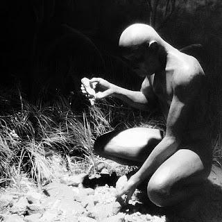 Homem primitivo, agachado, tritura sementes com pedaço de pedra.