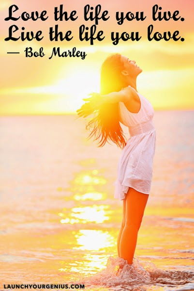 """Love the life you live. Live the life you love."" ~ Bob Marley Picture of women standing in ocean with arms outstreched and the sun rising behind her."