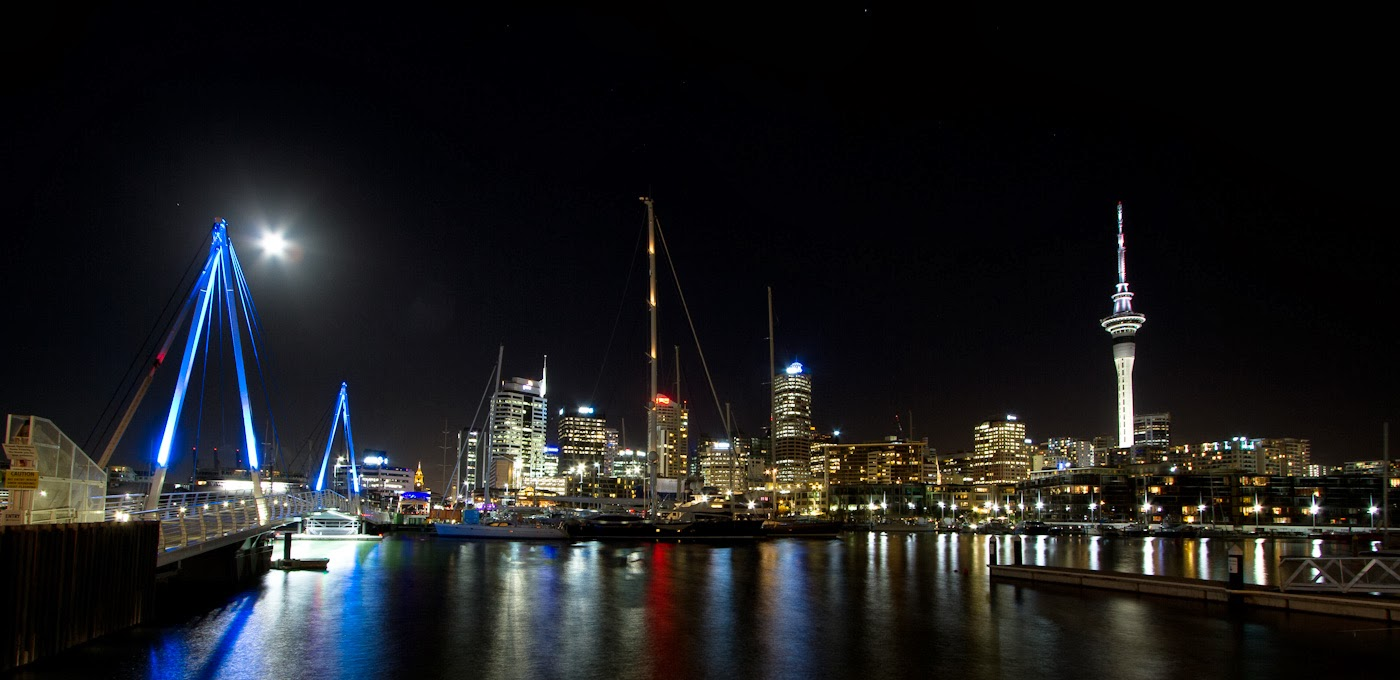 Yacht and sky tower from the harbor at night