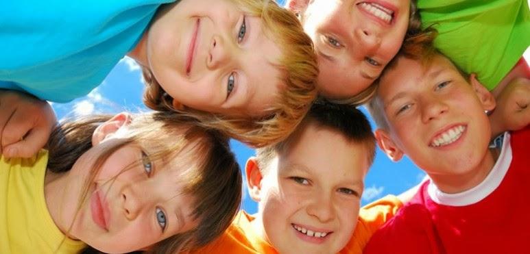 grupo de 5 niños uniendo sus cabezas para formar un circulo