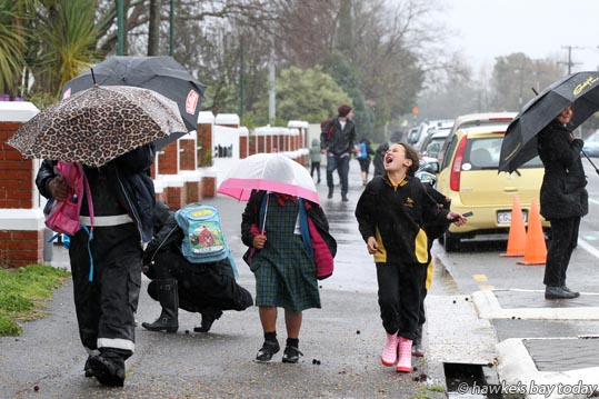 Parents, caregivers and kids with umbrellas after school at Mahora School, Frederick St, Hastings. photograph