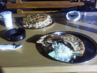 Two plates with bread containing kebabs and onions, and a glass of yogurt in Sarajevo, Bosnia.