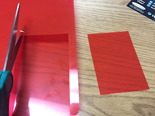 Scissors cutting a red plastic folder into small rectangles.