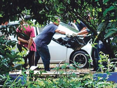 Anggota polis mengangkat keluar mayat dari kereta untuk dibawa ke hospital bagi proses bedah siasat.