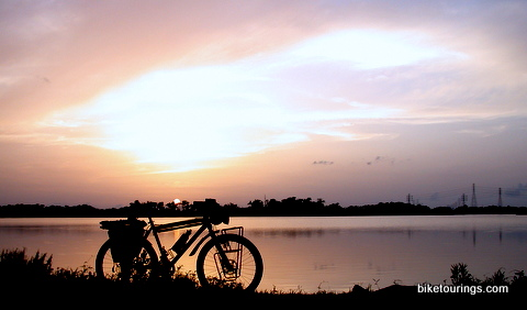 Picture of touring bike with sunset over bay