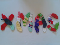 Xmas spelled out with colourful knitted mini Christmas stockings